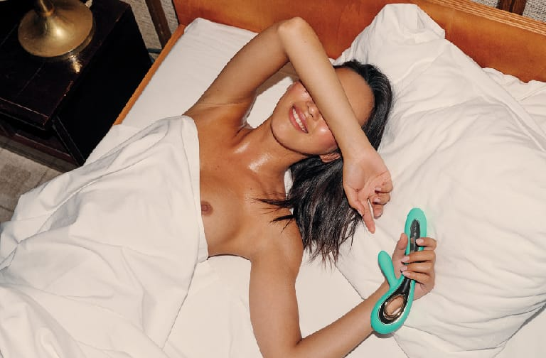 Woman in a bed covering her eyes while holding the LELO Soraya 2
