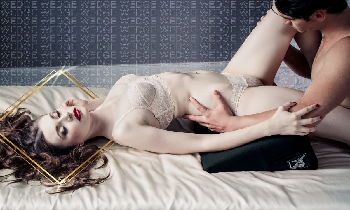 Model lying on the Liberator Wedge Sex Pillow