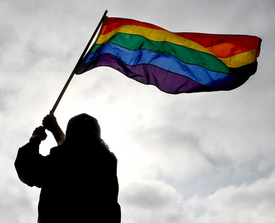 silhouette of person holding rainbow flag